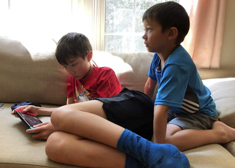 Billy Nuckols, 10, plays video games while his brother Jimmy, 6, watches TV at home in Burke, Va., July 19, 2020. The activities are a major part of their daily routine during the coronavirus pandemic. (AP Photo/Ben Nuckols)