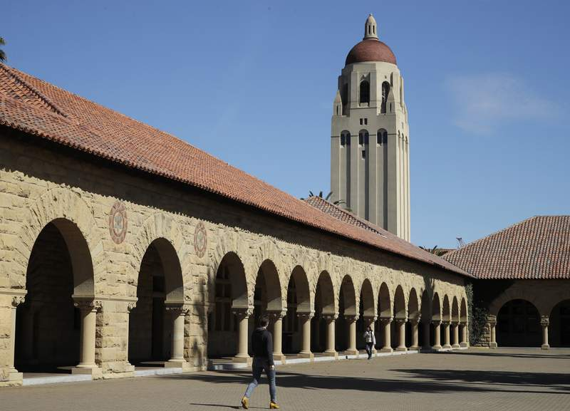FILE- In this March 14, 2019, file photo, people walk on the Stanford University campus beneath Hoover Tower in Stanford, Calif. A week after revoking sweeping new restrictions on international students, federal immigration officials on Friday, July 24, 2020, announced that new foreign students will be barred from entering the United States if they plan to take their classes entirely online this fall. (AP Photo/Ben Margot, File)