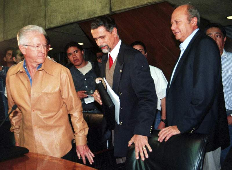 FILE - In this Sept. 29, 2000 file photo, leader of Mexico's oil workers union Carlos Romero Deschamps, right, Labor Secretary Carlos Maria Abascal, center, and Pemex director Raul Munoz Leos, arrive at a press conference in Mexico City.  Romero Deschamps will finally be resigning from his symbolic post as a worker at Mexico's state-owned oil company Pemex, President Andrs Manuel Lpez Obrador announced Tuesday, March 16, 2021. (AP Photo/Ismael Rojas, File)
