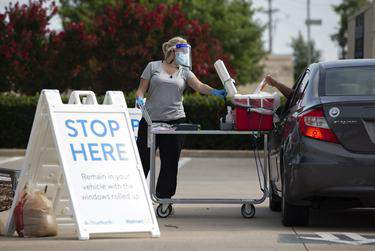 Pharmacist Emily Smith opens a cooler for a patient to place their self-swab coronavirus test at a Walmart drive thru testing site in McKinney on June 29.      Shelby Tauber