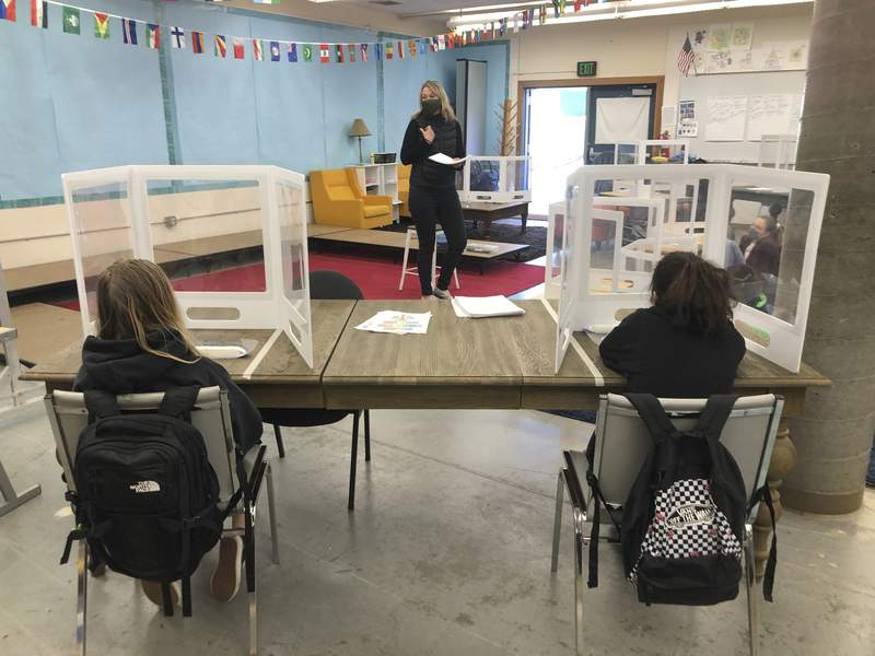 FILE - In this March 2, 2021, file photo, science teacher Jennifer Becker, center, at the Sinaloa Middle School talks to her students who are distanced at their desks in Novato, Calif. Gov. Gavin Newsom signed a new law Friday, March 5, with $6.6 billion in incentives to try to get more California schools to reopen. The response has been lukewarm support, as teachers resist and parents complain that it doesn't do enough to get kids in the classroom. (AP Photo/Haven Daley, File)