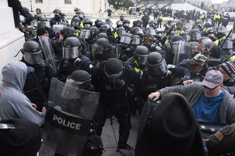 """FILE - In this Jan. 6, 2021, file photo, U.S. Capitol Police push back rioters trying to enter the U.S. Capitol in Washington. A former State Department aide in President Donald Trumps administration has been charged with participating in the deadly siege at the Capitol. Court papers say Federico Klein was seen wearing a Make America Great Again"""" hat amid the throng of people trying to force their way into the Capitol. Authorities say Klein pushed his way toward the doors, where he physically and verbally engaged with officers trying to keep the mob back. Klein resigned from his position on Jan. 19, the day before Joe Biden was sworn in as president. (AP Photo/Jose Luis Magana, File)"""