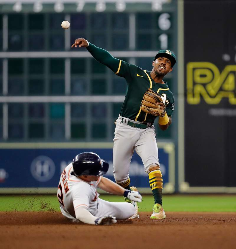 HOUSTON, TEXAS - JULY 08: Tony Kemp #5 of the Oakland Athletics turns a double play as Myles Straw #3 of the Houston Astros slides into second base in the ninth inning at Minute Maid Park on July 08, 2021 in Houston, Texas. (Photo by Bob Levey/Getty Images)