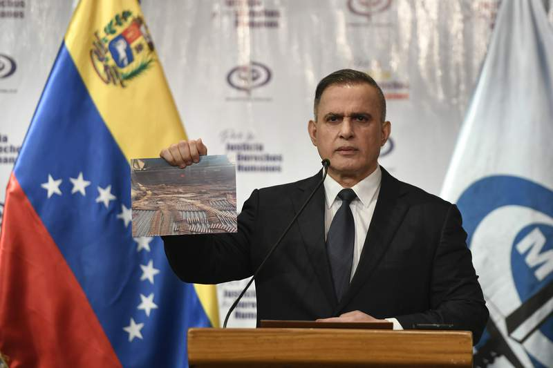 Venezuela's Attorney General Tarek William Saab holds a photo of bullets he says were seized with other weapons in connection with what the government calls a failed attack over the weekend aimed at overthrowing President Nicols Maduro, during a press conference in Caracas, Venezuela, Friday, May 8, 2020. (AP Photo/Matias Delacroix)
