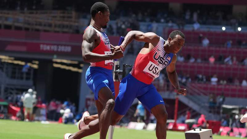 Fred Kerley (USA), left, and Ronnie Baker (USA) exchange on the 4x100m relay round 1 heat 2 during the Tokyo 2020 Summer Olympic Games at Olympic Stadium.