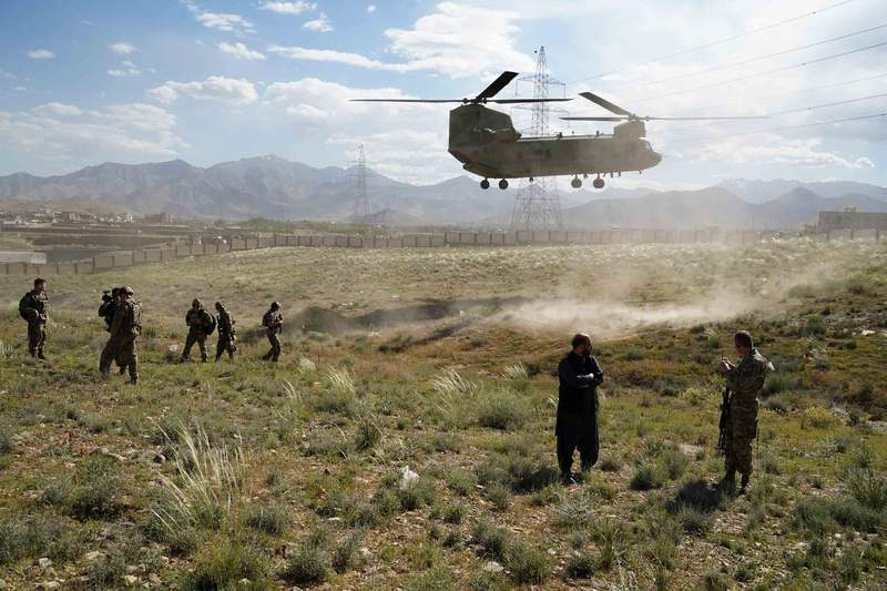 A US military Chinook helicopter lands on a field outside the governor's palace in Maidan Shar, capital of Wardak province, Afghanistan on June 6, 2019.
