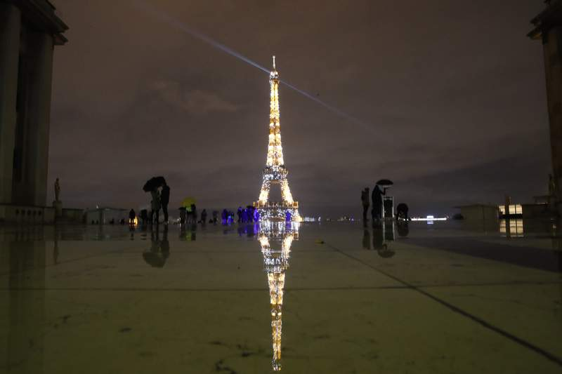 People stroll on the Trocadero square to watch the Eiffel Tower lightings, Friday, Dec. 11, 2020 in Paris. (AP Photo/Francois Mori)