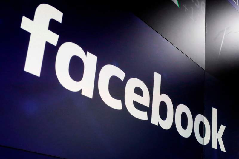 FILE- In this March 29, 2018, file photo, the logo for Facebook appears on screens at the Nasdaq MarketSite in New York's Times Square. A senior Federal Trade Commission official is criticizing Facebooks move to shut down the personal accounts of two academic researchers and terminate their probe into misinformation spread through political ads on the social network, Thursday, Aug. 5, 2021. (AP Photo/Richard Drew, File)