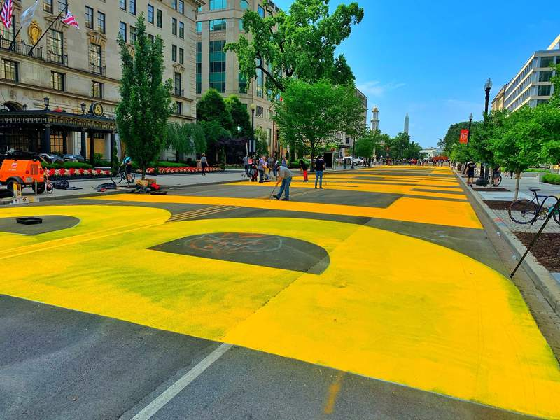 Giant, yellow letters are painted on a busy Washington D.C. street spelling out  BLACK LIVES MATTE