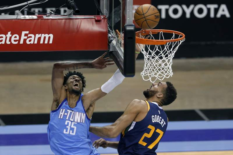 Houston Rockets center Christian Wood (35) puts up a shot past Utah Jazz center Rudy Gobert (27) during the first half of an NBA basketball game Wednesday, April 21, 2021, in Houston. (AP Photo/Michael Wyke, Pool)