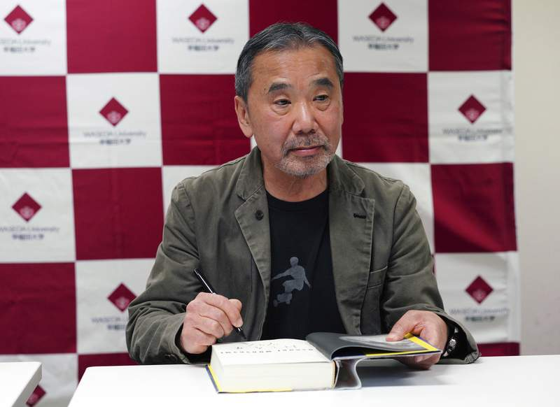 """FILE - In this Nov. 3, 2018, file photo, Japanese novelist Haruki Murakami signs his autograph on his novel """"Killing Commendatore"""" during a press conference at Waseda University in Tokyo. The acclaimed Japanese novelist Murakami, hosting a special radio show from home, painted a brighter side of the world with his favorite music, and said Friday, May 22, 2020, the fight against the coronavirus is a challenge to human wisdom in figuring out ways to help and care each other. (AP Photo/Eugene Hoshiko, File)"""