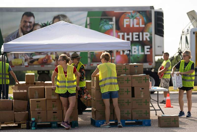 Central Texas Food Bank volunteers prepare to distribute free food to help people facing increasing food insecurity at the Travis County Expo Center in Austin on July 1, 2021.