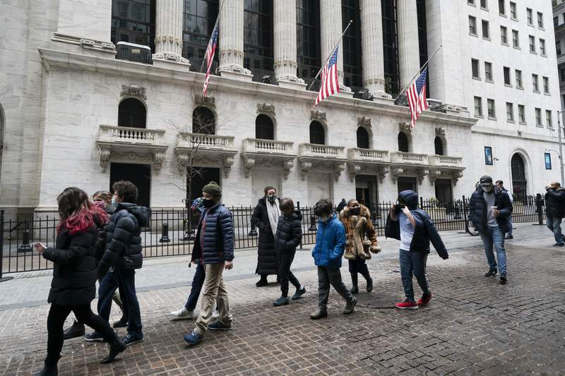A school group walks by the New York Stock Exchange, Tuesday, Feb. 23, 2021.  Major indexes are off to a mixed start on Wall Street as gains for banks and industrial companies are offset by losses in Big Tech stocks like Apple and Amazon. The S&P 500 was down 0.2% in the first few minutes of trading Wednesday, a day after it narrowly managed to break a five-day losing streak.   (AP Photo/Mark Lennihan)