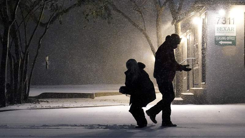 Two people play in the snow in San Antonio, Sunday, Feb. 14, 2021. Snow and ice blanketed large swaths of the U.S. on Sunday, prompting canceled flights, making driving perilous and reaching into areas as far south as Texas' Gulf Coast, where snow and sleet were expected overnight. (AP Photo/Eric Gay)