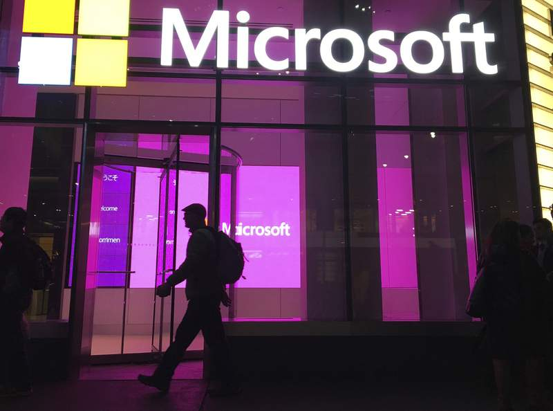 FILE - In this Nov. 10, 2016, photo, people walk near a Microsoft office in New York.  Microsoft is telling employees Thursday, Sept. 9, 2021, that their return to U.S. offices is delayed indefinitely until its safer to do so. Given the uncertainty of COVID-19, weve decided against attempting to forecast a new date for a full reopening of our U.S. work sites, corporate vice president Jared Spataro wrote in a blog post. (AP Photo/Swayne B. Hall)