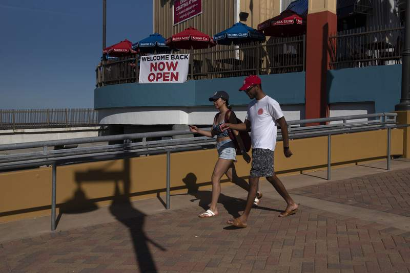 GALVESTON, TX - MAY 01: People walk along Pleasure Pier after beaches were reopened on May 1, 2020 in Galveston, Texas. As part of phase one Gov. Greg Abbott reopened the beaches to the public Friday along with restaurants and retailers. (Photo by Callaghan O'Hare/Getty Images)