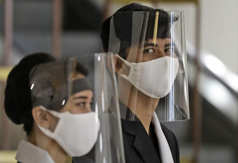 Staff wear face shields as a precaution against the new coronavirus at the reception desk of Senayan City shopping mall in Jakarta, Indonesia, Tuesday, June 9, 2020. As Indonesia's overall virus caseload continues to rise, the capital city has moved to restore normalcy by lifting some restrictions this week, saying that the spread of the virus in the city of 11 million has slowed after peaking in mid-April. (AP Photo/Dita Alangkara)