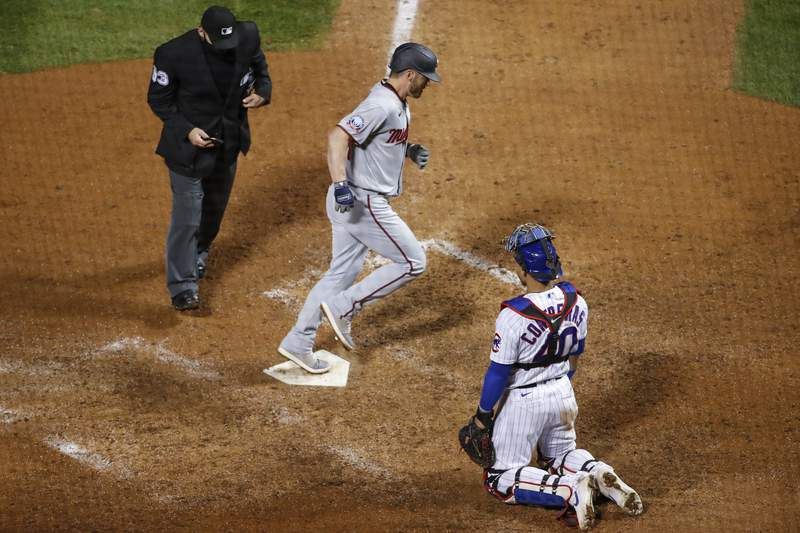 Minnesota Twins' Josh Donaldson, center, crosses home plate after hitting a solo home run off Chicago Cubs relief pitcher Dan Winkler during the ninth inning of a baseball game, Saturday, Sept. 19, 2020, in Chicago. (AP Photo/Kamil Krzaczynski)