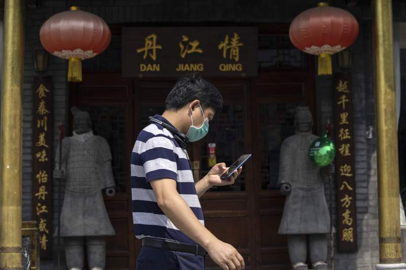 A man wearing a mask to curb the spread of the coronavirus walks past replicas of the Terracotta Warriors outside a restaurant in Beijing on Wednesday, July 8, 2020. (AP Photo/Ng Han Guan)