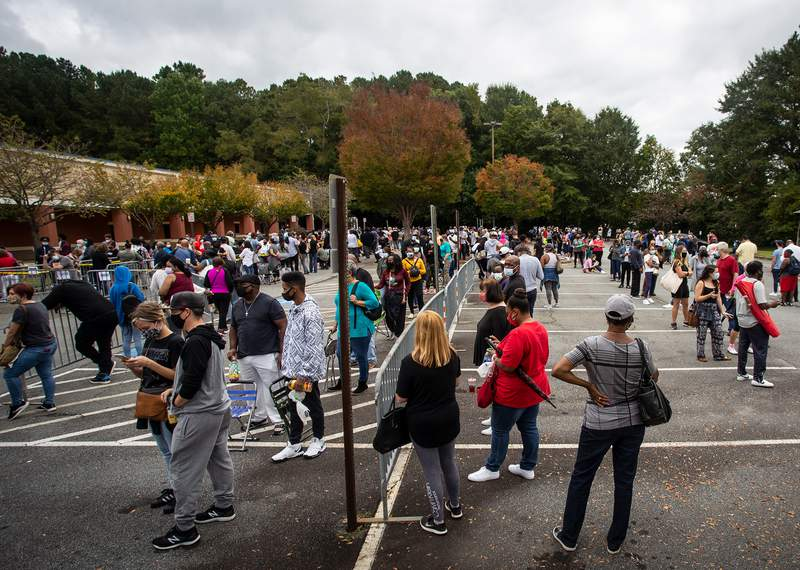 Hundreds of people wait in line for early voting on Monday, Oct. 12, 2020, in Marietta, Georgia. Eager voters have waited six hours or more in the former Republican stronghold of Cobb County, and lines have wrapped around buildings in solidly Democratic DeKalb County. (AP Photo/Ron Harris)
