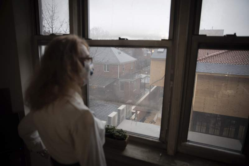 FILE - In this Thursday, March 18, 2021 file photo, Bonney Ginett looks out the window of her apartment in the Queens borough of New York. Ginett, whose massage therapy business dried up during the pandemic, applied for help in July and said she was denied in October because she failed to prove loss of income. The 65-year-old New York City resident now owes more than $26,000 in back rent on her one-bedroom apartment and fears eviction. (AP Photo/Robert Bumsted)