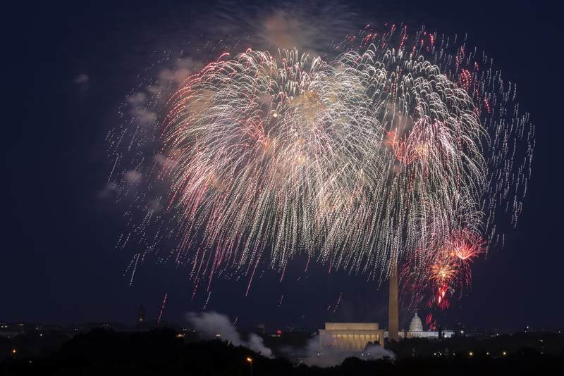 FILE - In this Saturday, July 4, 2020, file photo, Fourth of July fireworks explode over the Lincoln Memorial, the Washington Monument and the U.S. Capitol along the National Mall in Washington. President Joe Biden wants to imbue Independence Day with new meaning in 2021 by encouraging nationwide celebrations to mark the countrys effective return to normalcy after 16 months of pandemic disruption. The White House says the National Mall in Washington will host the traditional fireworks ceremony and it's encouraging other communities hold festivities as well. (AP Photo/Cliff Owen, File)