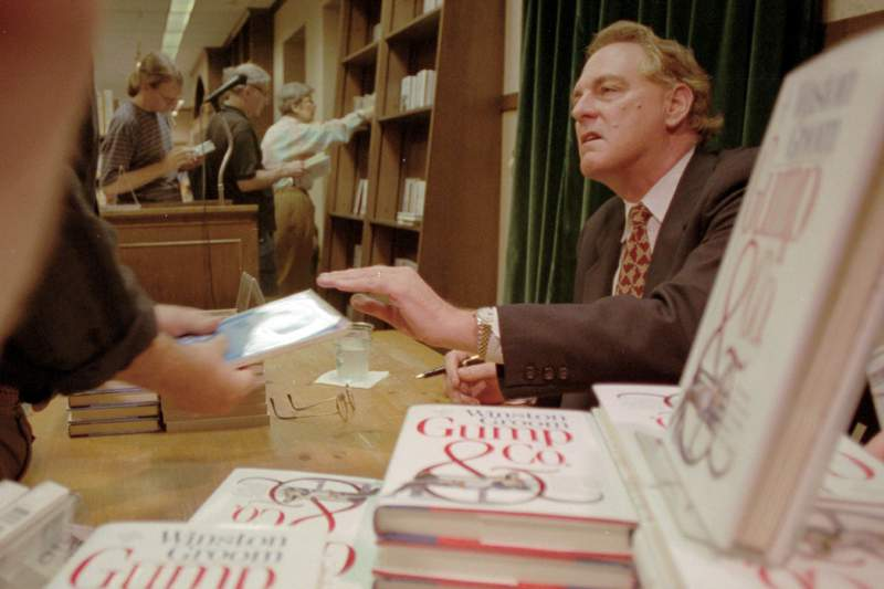 """FILE - In this Aug. 21, 1995, file photo, Winston Groom, author of """"Forrest Gump,"""" the book on which the film was based, signs copies of """"Gump & Co.,"""" the sequel to """"Forrest Gump"""", at a New York City bookstore. Groom, the author of the novel """"Forrest Gump"""" that was made into a six-Oscar winning 1994 movie that became a soaring pop culture hit, has died, an Alabama official close to the writer said Thursday, Sept. 17, 2020. He was 77. (AP Photo/Anders Krusberg, File)"""