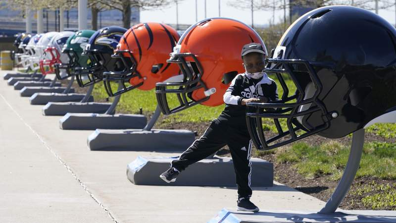 Joseph Toliver, 4, plays on one of the 32 NFL team helmets on display, Tuesday, April 13, 2021, in downtown Cleveland. Forced to cancel last year's NFL Draft in Las Vegas, the league is using lessons learned while plowing through an unprecedented, socially-distanced 2020 season and holding the Super Bow in Tampa, to have a draft that will look much more like normal  well, the new normal  with fans wearing their favorite team's colors and required masks.(AP Photo/Tony Dejak)