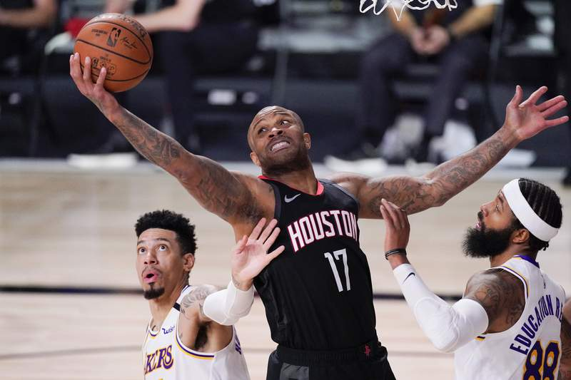 Houston Rockets' P.J. Tucker (17) grabs a rebound between Los Angeles Lakers' Danny Green, left, and Markieff Morris during the first half of an NBA conference semifinal playoff basketball game Saturday, Sept. 12, 2020, in Lake Buena Vista, Fla. (AP Photo/Mark J. Terrill)