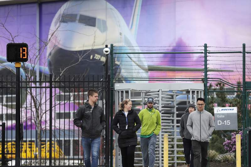 FILE - In this March 23, 2020, file photo, workers head out a gate at a Boeing airplane manufacturing plant, where a mural of a jet covers a massive door behind in Renton, Wash. Boeing Co. has said it will dole out annual performance bonuses next month to most employees despite losing $12 billion over the last year during the coronavirus pandemic. Most of the company's employees did not receive annual bonuses last year after it lost $636 million in 2019 because of the grounding of the 737 MAX by the Federal Aviation Administration, The Seattle Times reported. (AP Photo/Elaine Thompson, File)