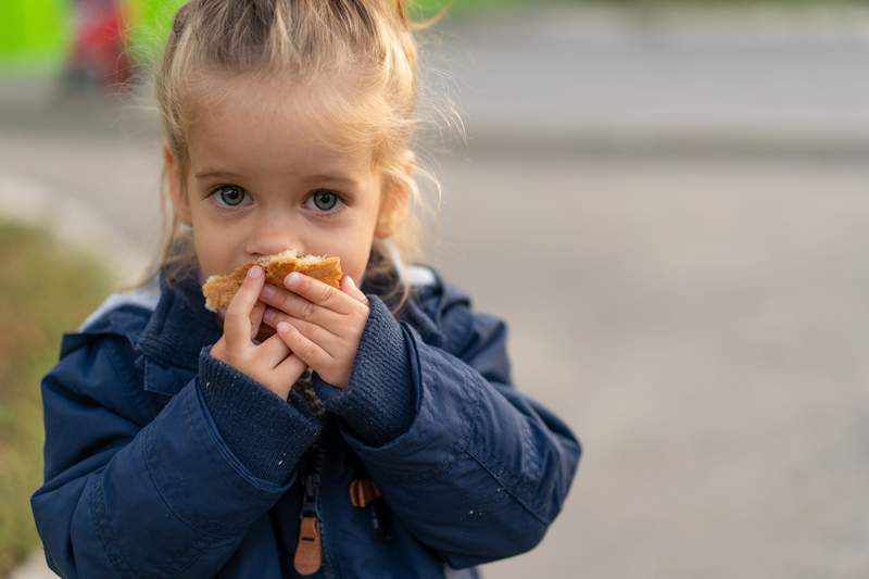 A beautiful little Caucasian girl with blond hair and eating bread eagerly with her hands looks at the camera with sad eyes, an abandoned child and hungry.