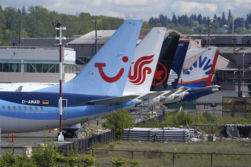 Boeing 737 Max airplanes, including one belonging to TUI Group, left, sit parked at a storage lot, Monday, April 26, 2021, near Boeing Field in Seattle.  Lawmakers, on Tuesday, May 18,  are asking Boeing and the Federal Aviation Administration for records detailing production problems with two of the company's most popular airliners. The lawmakers are focusing on the Boeing 737 Max and a larger plane, the 787, which Boeing calls the Dreamliner.  (AP Photo/Ted S. Warren)