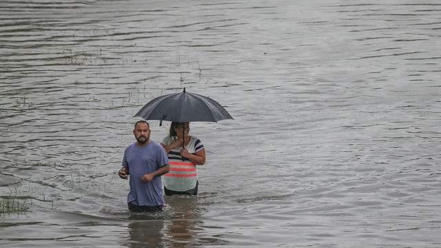 People walk through water onHopper Roadon Sept. 19, 2019, in Houston.