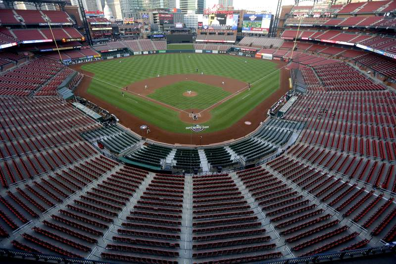 FILE - In this July 24, 2020, file photo, empty seats are viewed in Busch Stadium as St. Louis Cardinals starting pitcher Jack Flaherty throws in the first inning baseball game against the Pittsburgh Pirates in St. Louis. Major League Baseball players rejected a proposal to delay the start of spring training and the season due to the coronavirus pandemic, vowing Monday, Feb. 1, 2021, to report under the original schedule. (AP Photo/Jeff Roberson, File)