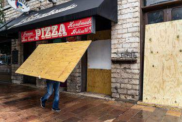 Workers boarded up bars on Sixth Street in Austin after Gov. Greg Abbott closed bars in Texas for the second time in three months because of the COVID-19 pandemic on June 26, 2020.      Jordan Vonderhaar for The Texas Tribune