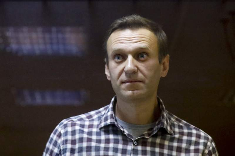 FILE - In this file photo taken on Saturday, Feb. 20, 2021, Russian opposition leader Alexei Navalny stands in a cage in the Babuskinsky District Court in Moscow, Russia.  Russian authorities have levied new criminal charges against imprisoned opposition leader Alexei Navalny. Russia's Investigative Committee on Wednesday Aug. 11, 2021, said it has charged Navalny with creating a non-profit organization that infringes on people's rights, a criminal offense punishable by up to four years in prison. (AP Photo/Alexander Zemlianichenko, File)