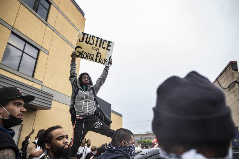 Protesters gather near the Minnesota Police 3rd Precinct during a gathering Tuesday, May 26, 2020, in response to the death the day before of George Floyd in police custody. Four Minneapolis officers involved in the arrest of Floyd, a black man who died in police custody, were fired Tuesday, hours after a bystanders video showed an officer kneeling on the handcuffed mans neck, even after he pleaded that he could not breathe and stopped moving. (Richard Tsong-Taatarii/Star Tribune via AP)