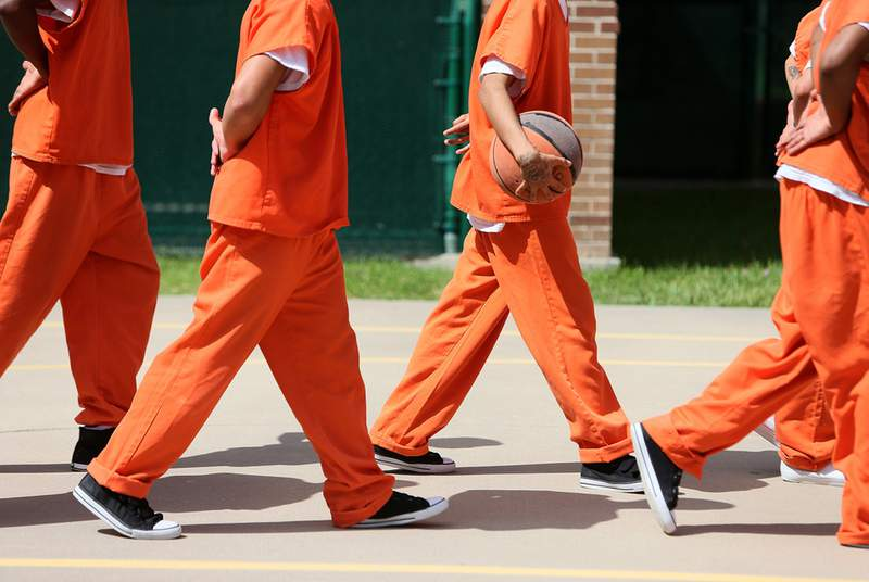 Detainees line up to leave the outdoor recreation area at the Travis County Juvenile Detention Center in Austin on June 24, 2013.