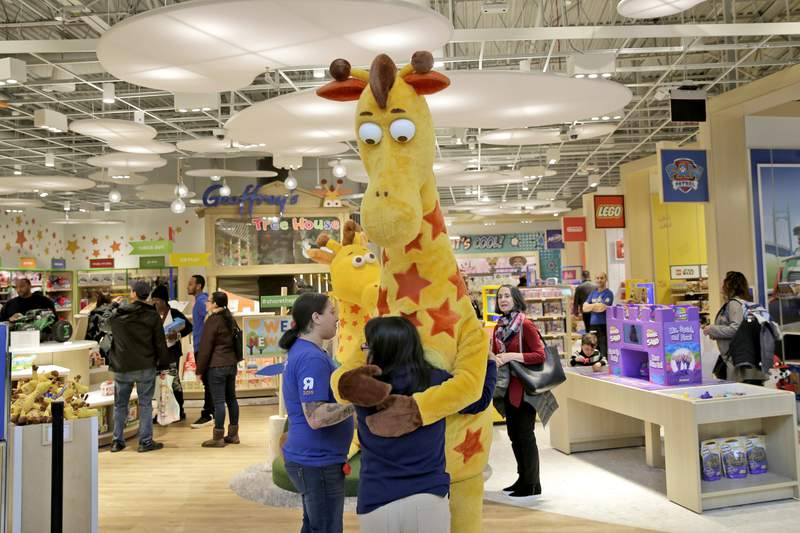 FILE - In this Dec. 9, 2019, file photo a girl hugs the Toys R Us mascot, Geoffrey, at the new store at a mall in Paramus, N.J  The only two Toys R Us stores that opened in November 2019 as part of a small U.S. comeback attempt by the iconic toy chain have now closed. The Toys R Us store at the Galleria mall in Houston shuttered on Jan. 15, while one at the Garden State Plaza in Paramus, New Jersey, closed on Tuesday, Jan. 26, 2021 according Tru Kids, a new entity formed when it acquired Toys R Us intellectual property during its liquidation in 2018.  (AP Photo/Seth Wenig)