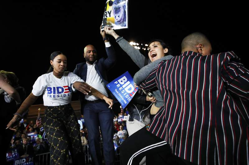 LOS ANGELES, CALIFORNIA - MARCH 03: A protestor (2nd R) charges the stage holding a sign that reads 'Let Dairy Die', as Democratic presidential candidate former Vice President Joe Biden speaks at a Super Tuesday campaign event at Baldwin Hills Recreation Center on March 3, 2020 in Los Angeles, California. After his make-or-break victory in South Carolina, Biden has continued to do well in the Super Tuesday primaries. (Photo by Mario Tama/Getty Images)