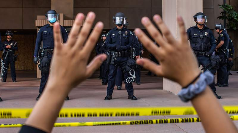 A demonstrator holds her hands up while she kneels in front of the Police at the Anaheim City Hall on June 1, 2020 in Anaheim, California, during a peaceful protest over the death of George Floyd. - Major US cities -- convulsed by protests, clashes with police and looting since the death in Minneapolis police custody of George Floyd a week ago -- braced Monday for another night of unrest. More than 40 cities have imposed curfews after consecutive nights of tension that included looting and the trashing of parked cars. (Photo by Apu GOMES / AFP) (Photo by APU GOMES/AFP via Getty Images)