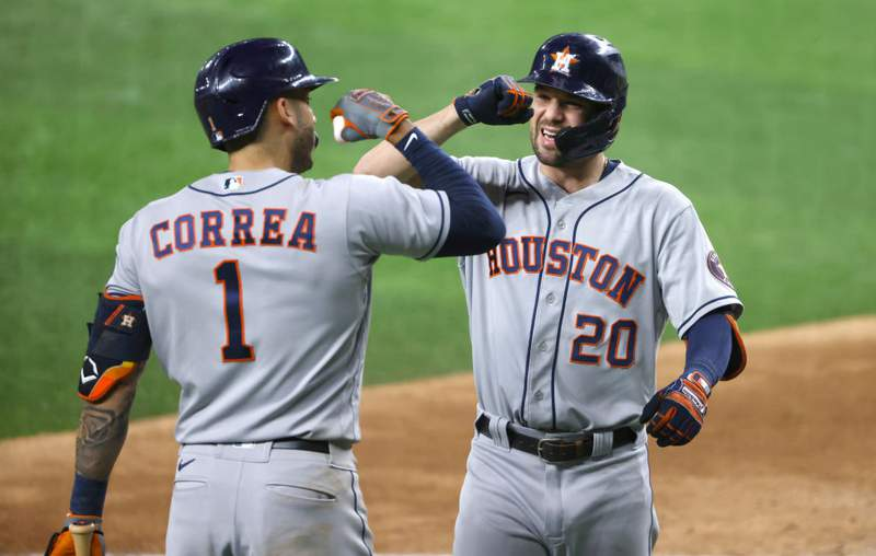 ARLINGTON, TX - SEPTEMBER 16: Chas McCormick #20 of the Houston Astros celebrates with teammate Carlos Correa #1 after hitting a two-run home run against the Texas Rangers during the eighth inning at Globe Life Field on September 16, 2021 in Arlington, Texas. (Photo by Ron Jenkins/Getty Images)