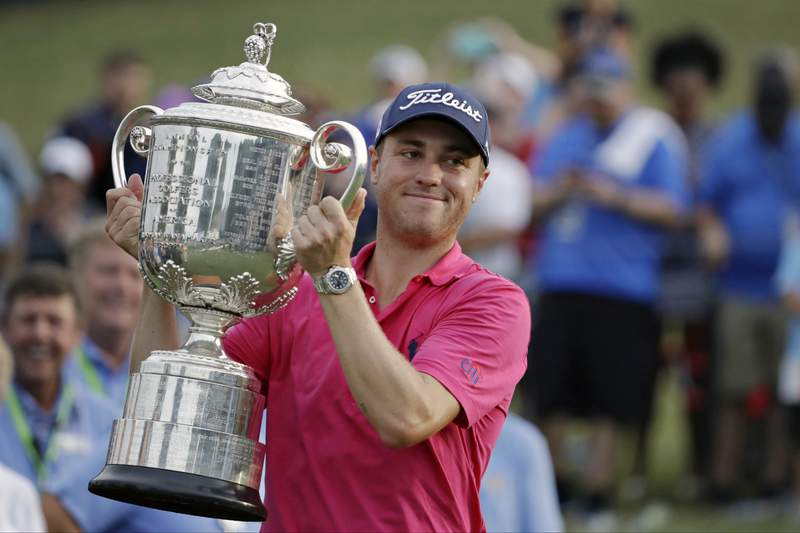 """FILE - In this Aug. 13, 2017, file photo, Justin Thomas poses with the Wanamaker Trophy after winning the PGA Championship golf tournament at the Quail Hollow Club in Charlotte, N.C. Justin Thomas can put down the driver and grab a controller: The former PGA Championship winner made the cover of the """"PGA Tour 2K21"""" video game. He's ready to tee off in the game on its Aug 21 release.(AP Photo/Chris O'Meara, File)"""