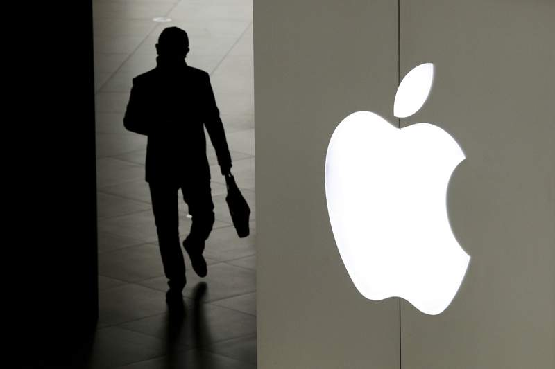 FILE - In this Jan. 3, 2019, file photo, a man leaves an Apple store in Beijing. Apple says it will roll out a new privacy control in spring 2021 to prevent iPhone apps from secretly shadowing people. (AP Photo/Andy Wong, File)