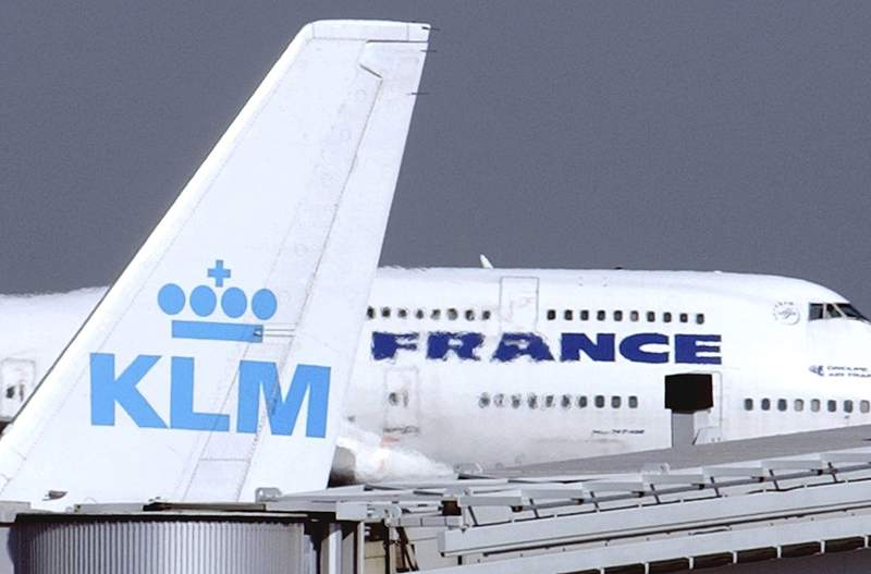 FILE - In this Sept. 30, 2003 file photo, an Air France jumbo jet rolls behind the tail of a KLM Royal Dutch airliner at Charles de Gaulle airport in Roissy, north of Paris. Pilots with Dutch national airline KLM agreed Tuesday, Nov. 3, 2020 to commit to accepting pay cuts for as long as the carrier needs a multibillion euro government coronavirus bailout, the pilots union and KLM announced. (AP Photo/Remy de la Mauviniere, File)