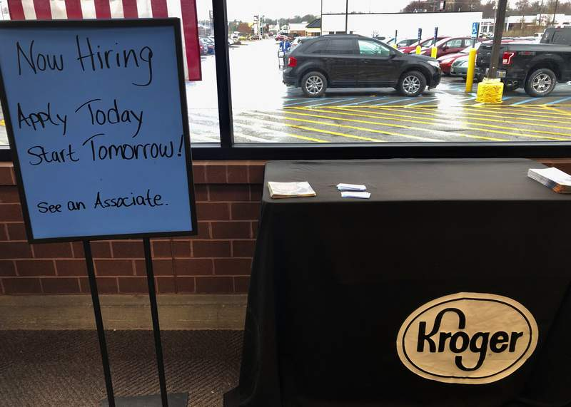 A sign encouraging job seekers to apply stands in a suburban Cincinnati Kroger store Wednesday, March 18, 2020. The Cincinnati-based supermarket chain is among those seeking help to keep up with cleaning and restocking during coronavirus outbreak.  (AP Photo/Dan Sewell)