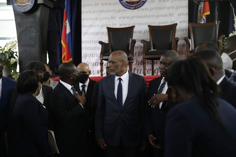 FILE - In this July 20, 2021 file photo, Prime Minister Ariel Henry, center, talks with former interim Prime Minister Claude Joseph as they stand surrounded by Henry's cabinet after his appointment in Port-au-Prince, Haiti, weeks after the assassination of President Jovenel Moise at his home. Henry faces increased scrutiny from authorities investigating Moises slaying. (AP Photo/Joseph Odelyn, File)