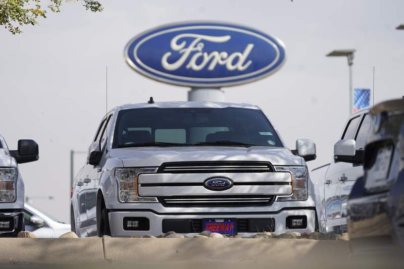 FILE - In this Sunday, Oct. 11, 2020, file photo, a row of 2020 sports-utility vehicles pickup trucks sits at a Ford dealership, in Denver. Ford Motor Co. lost $1.28 billion last year as it dealt with the coronavirus pandemic that forced it to shut down U.S. factories for about two months. But the automaker said Thursday, Feb. 4, 2021, it is generating strong cash flow and will go all-in on electric vehicles. (AP Photo/David Zalubowski, File)