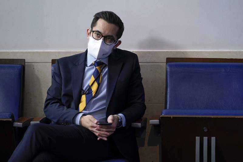 In this Feb. 9, 2021 photo, White House deputy press secretary TJ Ducklo listens as press secretary Jen Psaki speaks during a press briefing at the White House in Washington.  Ducklo has been suspended for a week without pay after he reportedly issued a sexist and profane threat to a journalist seeking to cover his relationship with another reporter.  (AP Photo/Patrick Semansky)