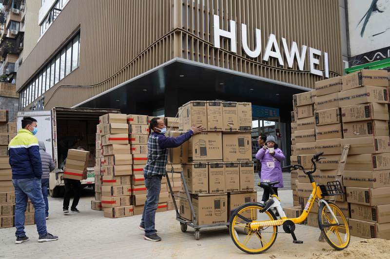 Workers move boxes of computers on a street of Wuhan in central China's Hubei province on Saturday, Jan. 16, 2021. China eked out 2.3% economic growth in 2020, likely becoming the only major economy to expand as shops and factories reopened relatively early from a shutdown to fight the coronavirus while the United States, Japan and Europe struggled with disease flare-ups. (AP Photo/Ng Han Guan)